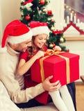 Contenitore di regalo sorridente di apertura della figlia e del padre Immagini Stock Libere da Diritti