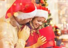 Contenitore di regalo sorridente di apertura della figlia e del padre Fotografia Stock