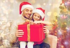 Contenitore di regalo sorridente di apertura della figlia e del padre Immagini Stock