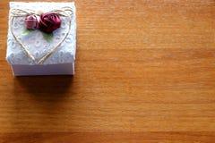 Contenitore di regalo su fondo di legno Scatola bianca con i fiori e nastro nella forma di cuore immagini stock