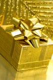 Contenitore di regalo su priorità bassa dorata Fotografie Stock Libere da Diritti