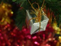 Contenitore di regalo sul ramo di pino e sul fondo del bokeh Fotografia Stock