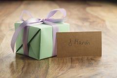 Contenitore di regalo verde con il fondo porpora di legno di arco con la cartolina d'auguri dell'8 marzo Fotografia Stock Libera da Diritti