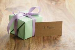 Contenitore di regalo verde con il fondo porpora di legno di arco con la cartolina d'auguri dell'8 marzo Immagini Stock