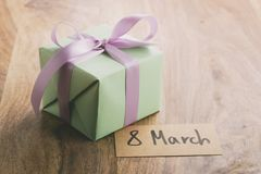 Contenitore di regalo verde con l'arco porpora del nastro sulla vecchia tavola di legno con la carta dell'8 marzo Fotografie Stock Libere da Diritti