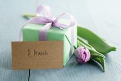 Contenitore di regalo verde con l'arco porpora e tulipano su fondo di legno blu con la cartolina d'auguri dell'8 marzo Immagini Stock