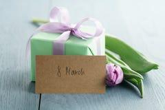 Contenitore di regalo verde con l'arco porpora e tulipano su fondo di legno blu con la cartolina d'auguri dell'8 marzo Immagini Stock Libere da Diritti