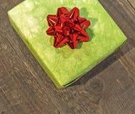 Contenitore di regalo verde con l'arco rosso isolato sulla tavola di legno Fotografia Stock