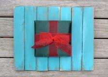 Contenitore di regalo verde con l'arco rosso su legno stagionato Fotografie Stock