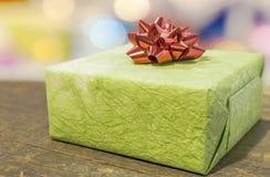 Contenitore di regalo verde con l'arco rosso sulla tavola di legno Immagini Stock