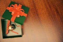 Contenitore di regalo verde con la campana di tintinnio dentro sul pavimento di legno Fotografia Stock