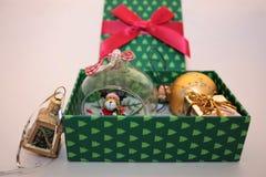 Contenitore di regalo verde di Natale con i presente su fondo leggero immagini stock