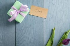Contenitore di regalo verde sulla tavola di legno blu con la carta di carta per l'8 marzo Fotografia Stock Libera da Diritti