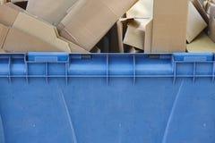 Contenitore di riciclaggio blu per carta con le scatole di cartone Fotografia Stock