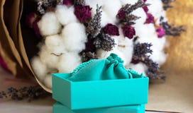 Contenitore di turchese per il presente sul fondo del fiore Immagini Stock Libere da Diritti