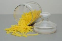 Contenitore di vetro con maccheroni sulla tavola grigia Immagini Stock Libere da Diritti