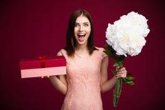 Contenitore e fiori di regalo svegli sorpresi della tenuta della donna Fotografia Stock Libera da Diritti