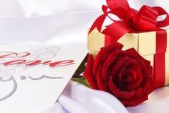 Contenitore e rose rosse di regalo dorati sul fondo bianco del raso Fotografia Stock Libera da Diritti