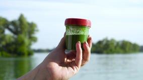 Contenitore femminile della tenuta della mano del primo piano con le alghe verdi e la rotazione un piccolo video d archivio