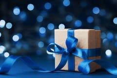 Contenitore o presente di regalo della festa con il nastro dell'arco contro il fondo blu del bokeh Cartolina d'auguri magica di n fotografia stock libera da diritti