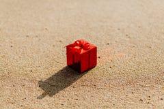 Contenitore rosso di regalo sulla spiaggia Immagini Stock Libere da Diritti