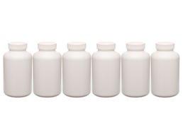 Contenitori bianchi delle pillole in una riga immagini stock