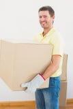 Contenitori commoventi di trasporto sorridenti di cartone dell'uomo a casa Immagine Stock