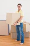Contenitori commoventi di trasporto sorridenti di cartone dell'uomo a casa Fotografia Stock