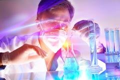 Contenitori del prodotto chimico e del ricercatore con le luci dietro la tavola fotografia stock libera da diritti