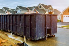 Contenitori dell'immondizia vicino alla nuova casa, contenitori rossi, riciclare e cantiere residuo sui precedenti Fotografie Stock Libere da Diritti