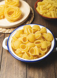 Contenitori della cucina con maccheroni e spaghetti circa da cucinare sulla tavola di legno Fotografie Stock Libere da Diritti