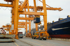 Contenitori di caricamento della gru della riva in nave del trasporto Immagine Stock