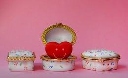 Contenitori di gioielli con uno che ha un cuore sorridente rosso dentro Fotografia Stock