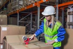 Contenitori di imballaggio del lavoratore del magazzino in deposito fotografia stock libera da diritti