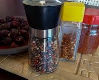 Contenitori di pepe inglese, fiocchi del peperoncino rosso, paprica e secco con riferimento a fotografia stock libera da diritti