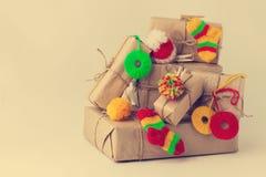 Contenitori di regali fatti a mano d'annata con i piccoli decori tricottati di Natale Fotografie Stock