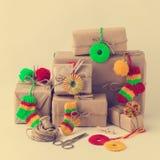 Contenitori di regali fatti a mano d'annata con i piccoli decori tricottati di Natale Fotografie Stock Libere da Diritti