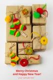Contenitori di regali fatti a mano d'annata con i piccoli decori tricottati di Natale Fotografia Stock