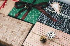 Contenitori di regalo avvolti alla moda, con le pigne dell'albero degli ornamenti e la t Immagini Stock