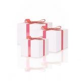 Contenitori di regalo bianchi con gli archi rossi del nastro, isolati su bianco Immagini Stock