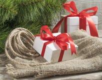 Contenitori di regalo bianchi con i nastri, la corda e il branc rossi dell'albero di Natale Immagini Stock