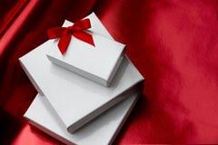Contenitori di regalo bianchi con l'arco rosso Immagine Stock Libera da Diritti