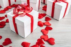 Contenitori di regalo bianchi sulle forme del cuore del tessuto e di un fondo grigio Immagini Stock