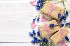 Contenitori di regalo con i fiori blu del muscari e cuori decorativi su wh Immagini Stock Libere da Diritti