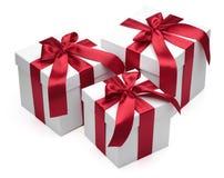 Contenitori di regalo con i nastri e gli archi rossi. Immagine Stock