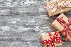 Contenitori di regalo con i nastri rossi su backgr di legno dipinto bianco nero Immagine Stock