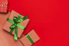 Contenitori di regalo con il nastro verde sulla disposizione rossa del piano di vista superiore del fondo Il concetto di festa, i fotografia stock libera da diritti