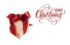 Contenitori di regalo con l'arco marrone su un fondo bianco e su un Buon Natale del testo Calligrafia dell'iscrizione Fotografie Stock