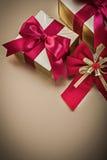 Contenitori di regalo con le feste rosse legate dell'arco dei nastri Fotografie Stock