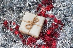 Contenitori di regalo con una grande decorazione rossa sul fondo d'argento del lamé Fiocchi di neve Regalo di Natale Priorità bas Fotografie Stock